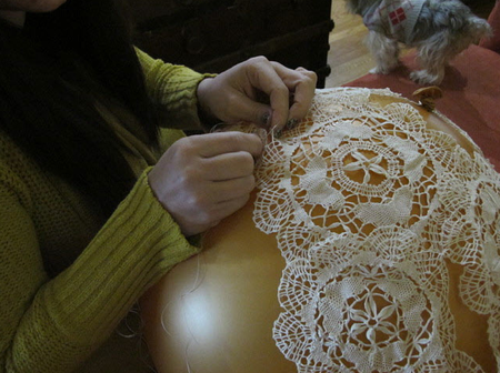 Sew the doilies around the balloon
